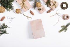 Украшения рождества на белой предпосылке: бумажная сумка, отруби ели Стоковая Фотография RF