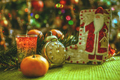 Украшения рождества - Санта Клаус, часы, tangerines и гирлянда Стоковое Фото
