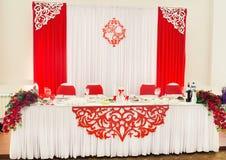 Украшения свадьбы белого и красного цвета на таблице для новобрачных Стоковое Изображение