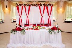 Украшения свадьбы белого и красного цвета на таблице для новобрачных Зала банкета торжества замужества Стоковая Фотография