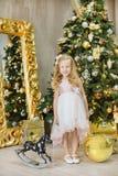 Украшения студии золота xmas рождества вскользь с милой девушкой и огромным зеркалом с золотыми настоящими моментами множества ра стоковая фотография