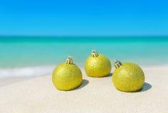 Украшения шариков сияющей рождественской елки Солнця золотые на песочном bea Стоковое Изображение