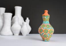Украшенная красочная ваза гончарни на предпосылке запачканных белых ваз Стоковые Фотографии RF