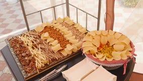 Украшенная поставляя еду таблица банкета с едой обломоков, чокнутого и различных видеоматериал