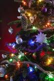 Украшенная рождественская елка со светами на красной предпосылке стоковое фото rf