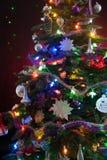 Украшенная рождественская елка со светами на красной предпосылке стоковое фото