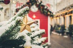 Украшенная рождественская елка с золотыми звездой и гирляндой на ярмарке напольно xmas конец вверх Зима стоковое фото rf