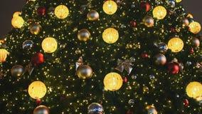 Украшенная рождественская елка в игрушках для рождества в Москве на улице Накаляя золотые шарики и гирлянды на сток-видео