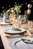 Украшенная таблица готовая для обедающего Красиво украшенная таблица установила с цветками, свечами, плитами и serviettes для wed стоковое фото rf