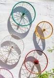 Украшенные красочные колеса велосипеда повиснули на белой стене Стоковое Фото