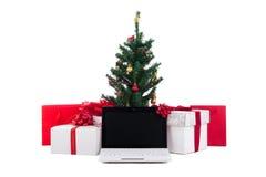 Украшенные рождественская елка, подарочные коробки и компьтер-книжка на белом backgro Стоковые Изображения