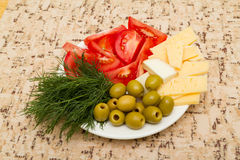 Укроп зеленых оливок томата сыра на белой плите на таблице Стоковое фото RF