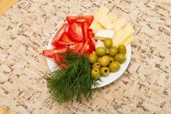 Укроп зеленых оливок томата сыра на белой плите на таблице Стоковые Изображения
