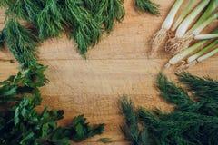 Укроп, петрушка и луки на деревянной разделочной доске взгляд сверху Плоское положение стоковая фотография rf