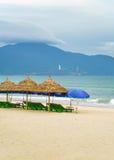 Укрытие и зонтики ладони с sunbeds в Китае приставают к берегу Стоковая Фотография