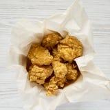 Укусы жареной курицы в бумажной коробке над белой деревянной поверхностью Плоское положение, накладные расходы, взгляд сверху : стоковые фото