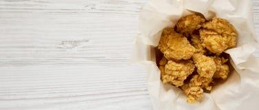 Укусы жареной курицы в бумажной коробке над белой деревянной предпосылкой, взглядом сверху Плоское положение, наверху, сверху r стоковые фотографии rf