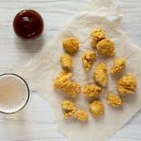 Укусы цыпленка, соус барбекю и стекло холодного пива на белой деревянной предпосылке, взгляда сверху r стоковое фото