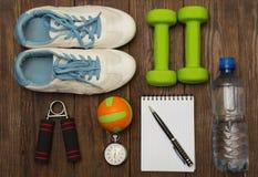 уклад жизни принципиальной схемы здоровый Гантель, рука детандера и шарик на деревенском деревянном столе Стоковые Изображения