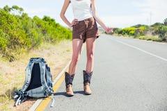 Укладывая рюкзак женщина на обочине thumbs вверх по представлять Стоковая Фотография