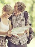 Укладывая рюкзак карта чтения пар на отключении Стоковая Фотография