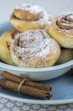 Улитки циннамона вызвали kanelbullar, очень вкусные сладостные крены в голубом шаре на скатерти цветочного узора, сырцовом циннам Стоковое Изображение