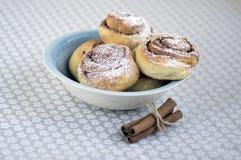 Улитки циннамона вызвали kanelbullar, очень вкусные сладостные крены в голубом шаре на скатерти цветочного узора, сырцовом циннам Стоковое Фото
