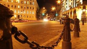 Улица города вечера, автомобили управляет, желтые красные светы, столбы цепей акции видеоматериалы