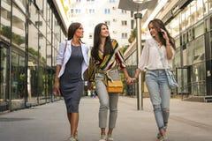 Улица женских друзей идя, держа руки стоковые изображения
