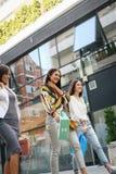 Улица 3 модных молодых женщин идя с хозяйственными сумками Стоковая Фотография