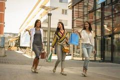 Улица 3 модных молодых женщин идя с хозяйственными сумками Стоковые Изображения RF