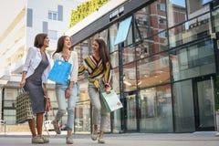 Улица 3 модных молодых женщин идя с хозяйственными сумками Стоковое Фото