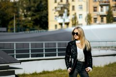Улица снятая прелестной белокурой модели с курткой и стеклами длинных волос нося Пустой космос стоковые фотографии rf