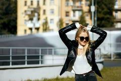 Улица снятая сногсшибательной белокурой девушки с курткой и стеклами длинных волос нося Пустой космос стоковое изображение