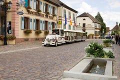Улица с туристским поездом в деревне Eguisheim во Франции стоковая фотография