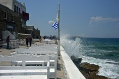 Улица Chora в Mykonos около моря с волнами и водой брызгает стоковое изображение rf