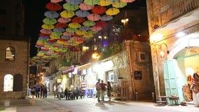 Улица Yoel Moshe Salomon в Иерусалиме, в историческом районе Nahalat Shiva на ноче, украшенной с ярко покрашенными зонтиками сток-видео