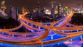 Улицы и пересечения Шанхая на ноче с Пудуном на заднем плане стоковое изображение