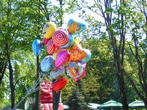 Уличный торговец продает красочные популярные воздушные шары гелия персонажа из мультфильма Стоковое фото RF
