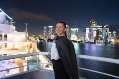 Улыбка бизнес-леди на доске корабля на ноче в miami, США Чувственная женщина в куртке костюма на горизонте города Мода, красота,  Стоковые Фотографии RF
