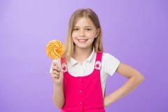 Улыбка девушки с леденцом на палочке на фиолетовой предпосылке Счастливый ребенк с карамелькой свирли на фиолетовой предпосылке у Стоковые Изображения