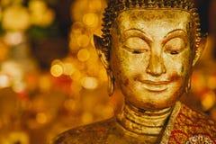 Улыбка золотого Будды, сторона золота Будды с предпосылкой bokeh, Таиландом, Азия, стоковое изображение