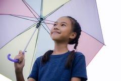 Улыбка зонтика владением ` s маленькой девочки и смотреть на сезон дождей стоковые фотографии rf