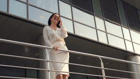 Улыбка и успех Молодая женщина говоря телефоном перед современными офисными зданиями движение медленное видеоматериал