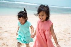 Улыбка 2 маленьких девочек при игре совместно на пляже стоковое изображение