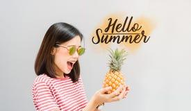 Улыбка маленькой девочки счастливые и жизнерадостные в красных платье и ананасе владением в руке, и имеют лето сообщения здравств Стоковая Фотография