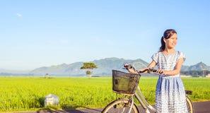 Улыбка маленькой девочки с велосипедом в поле Стоковая Фотография RF