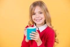 Улыбка ребенка с голубой чашкой на оранжевой предпосылке Стоковое фото RF