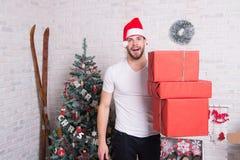 Улыбка santa человека с коробками на рождественской елке Стоковое Изображение RF