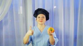 Улыбки женские повара, держат желтый перец в ее руке и показывают класс акции видеоматериалы
